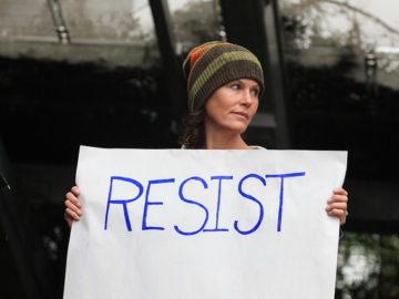 Protester holds resist sign at rally against President Trump African American Conservatives AACONS